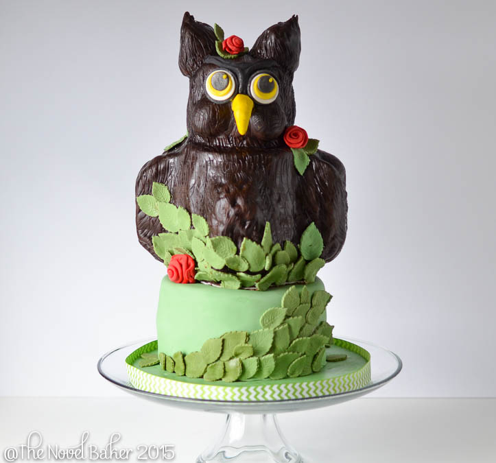 3 D owl cake with brown fondant and red roses perched upon a green cake covered in leaves