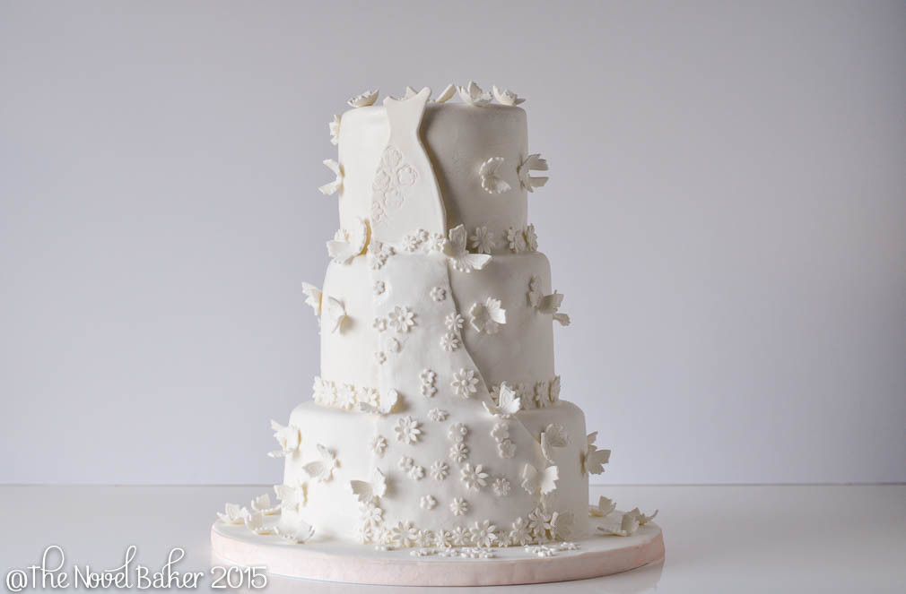 White Bridal Dress draped across two tiers of white fondant sprinkled with butterflies