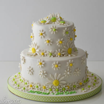 2-tier white cake with white and yellow daisies