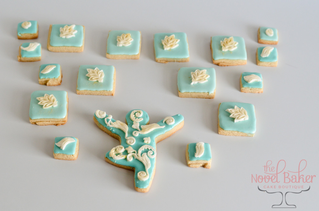 Sugar Cookies with Turquoise Royal Icing , white baby lotus flowers, and a center tree pose cookie