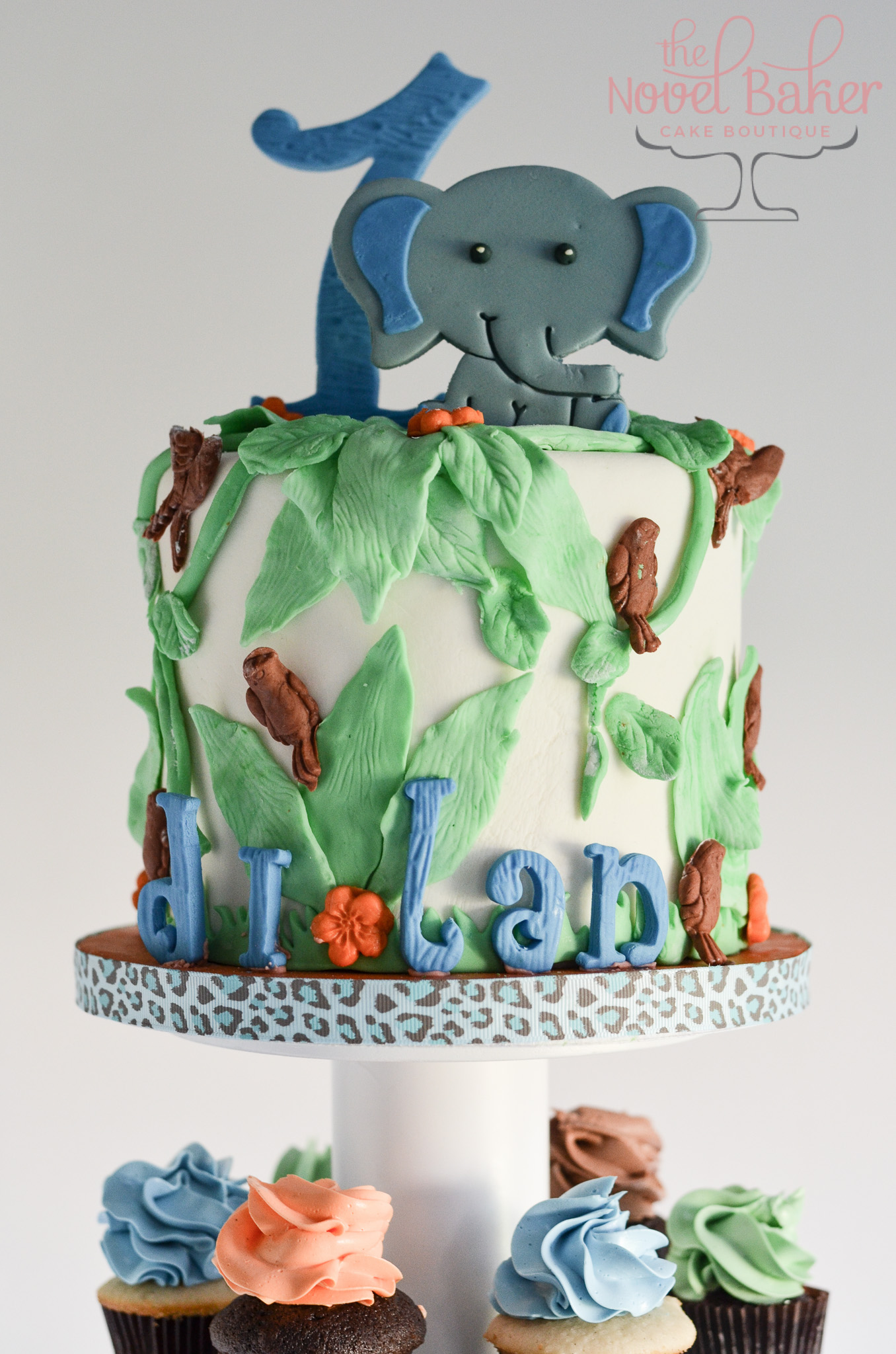 "Baby Elephant sits atop a white fondant cake covered in green vines, brown parrots and ""dilan"""