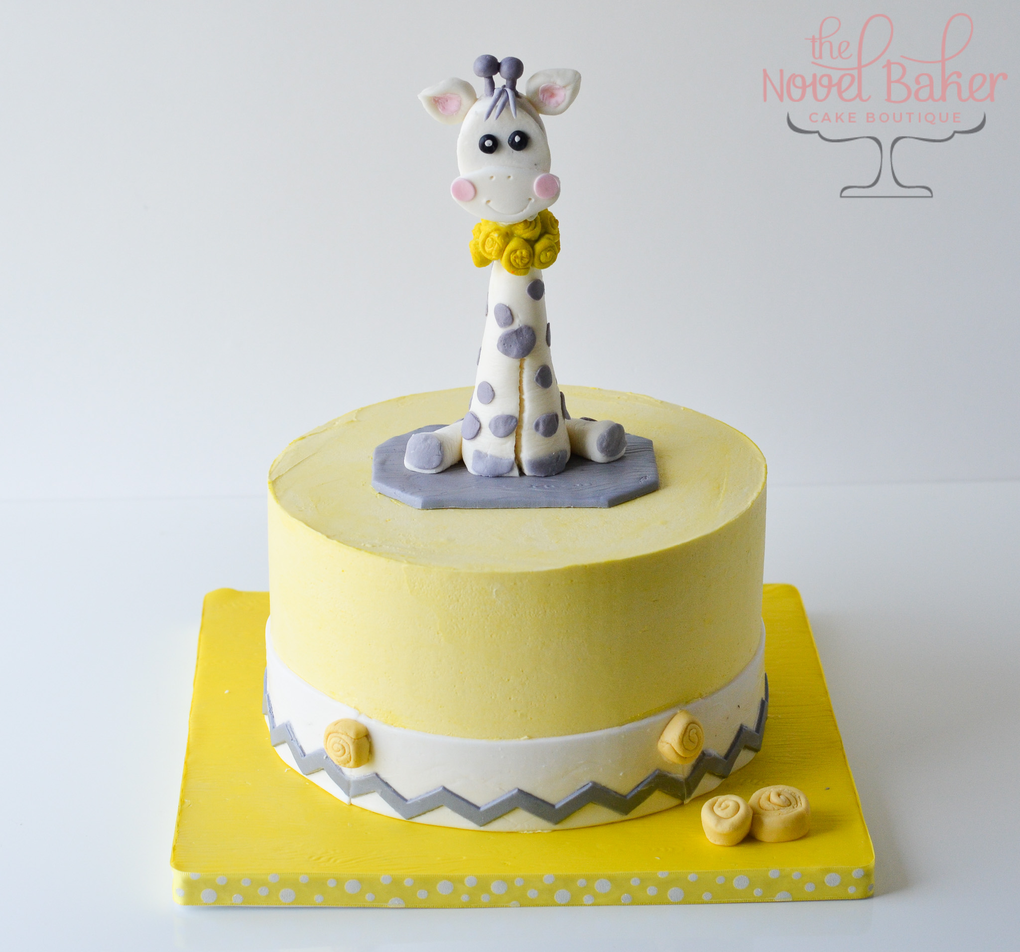 White and gray 3d baby giraffe on a yellow round cake with white band and gray chevron