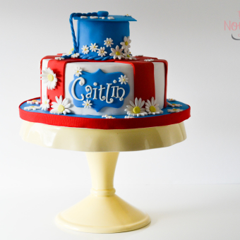 White Cake, Wide Red Stripes, Topped with a 3D Blue Grad Cap, sprinkled with Daisies