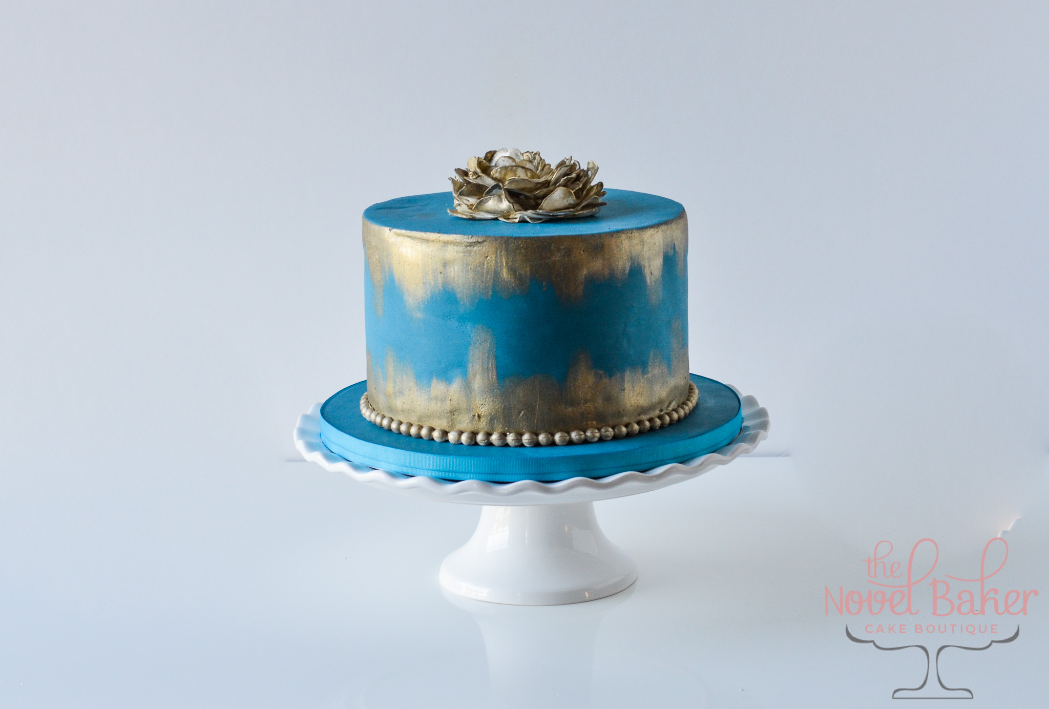 Deep Teal Blue single tier cake with painted gold strokes off the bottom and top tiers, gold pearl bottom border, stunning gold topper fantasy flower