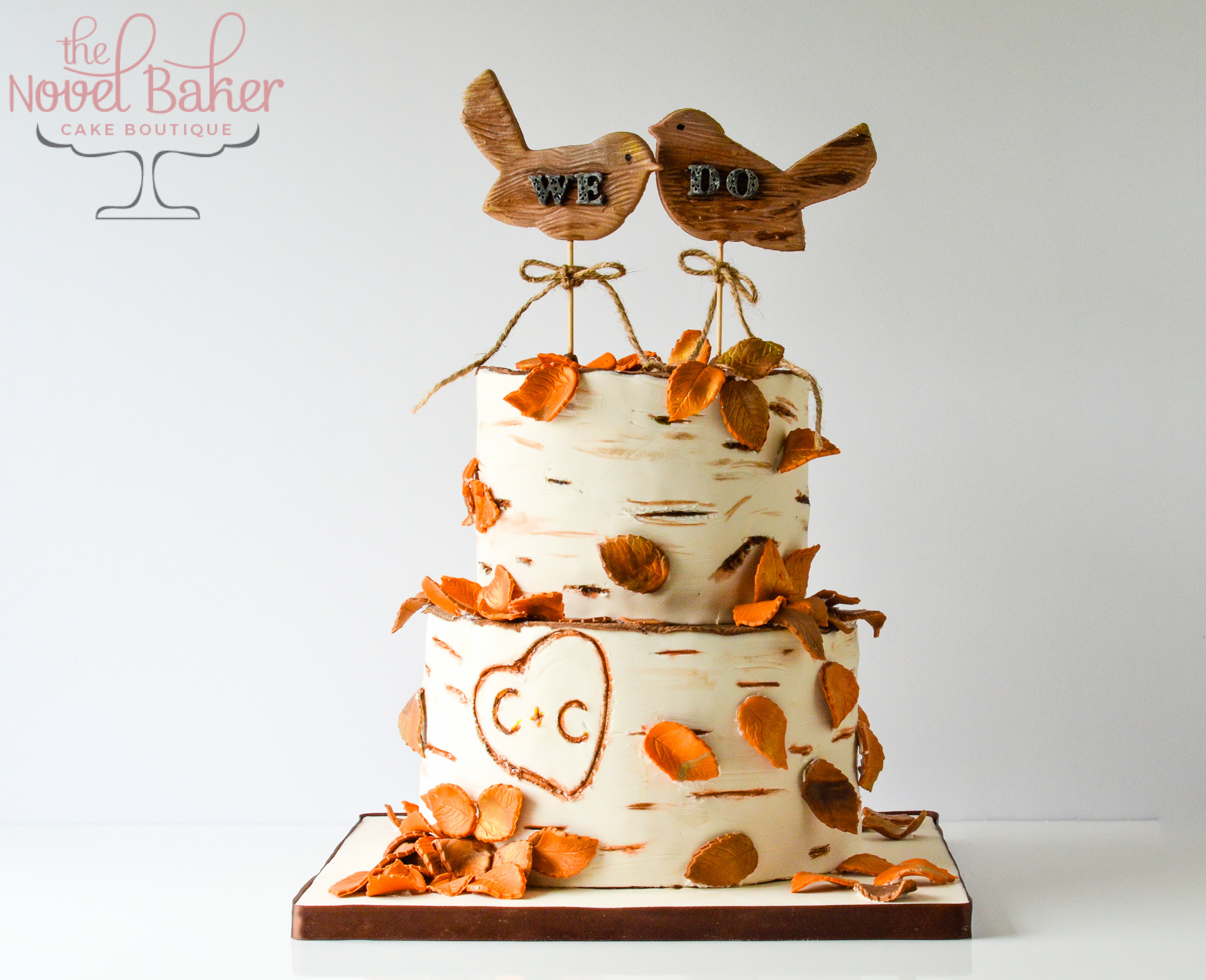 We Do Birds top a white birch cake with fall leaves and Initial heart