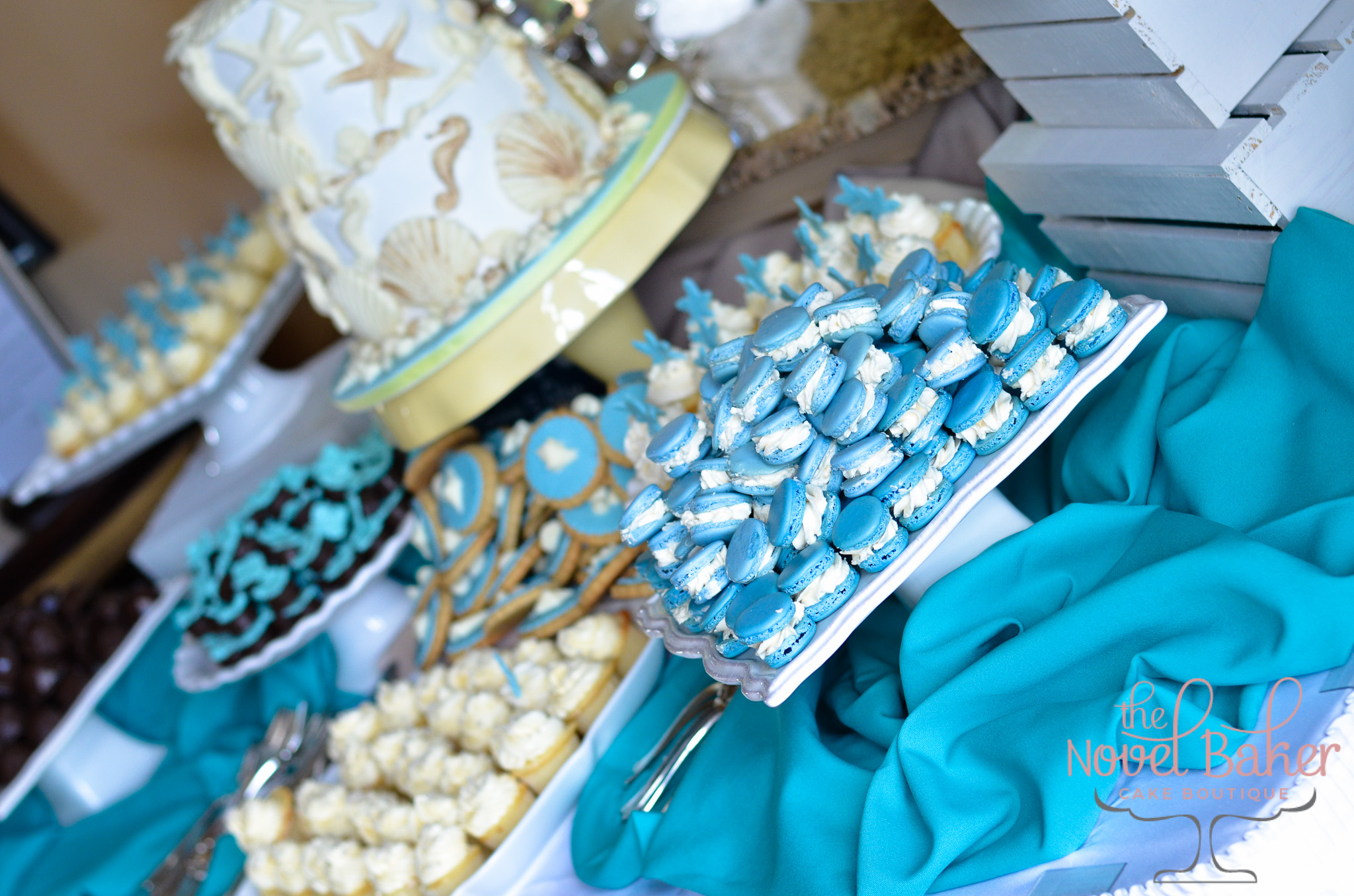 Two Tier SeaShell Cake, blue macarons, white cupcakes, blue and white seashell cookies.