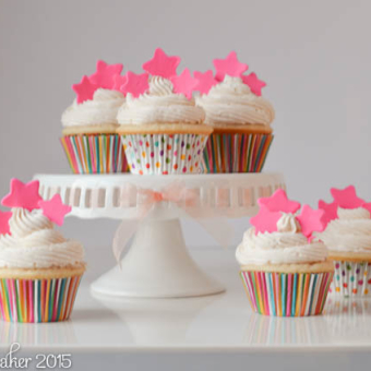 White Cupcakes in stripped and dotted liners topped with fuschia stars