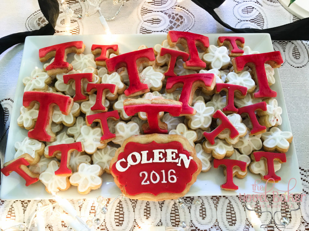 "Temple ""T"" cookies sprinkled across a base of white daisy cookies"