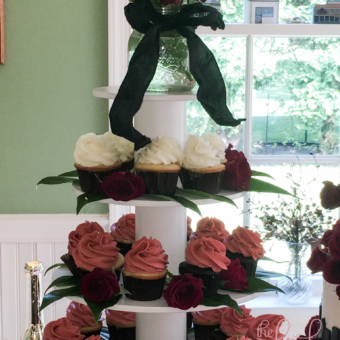 Red rose topped cupcake tower with chocolate & vanilla cupcakes with chocolate, vanilla and raspberry buttercreams.