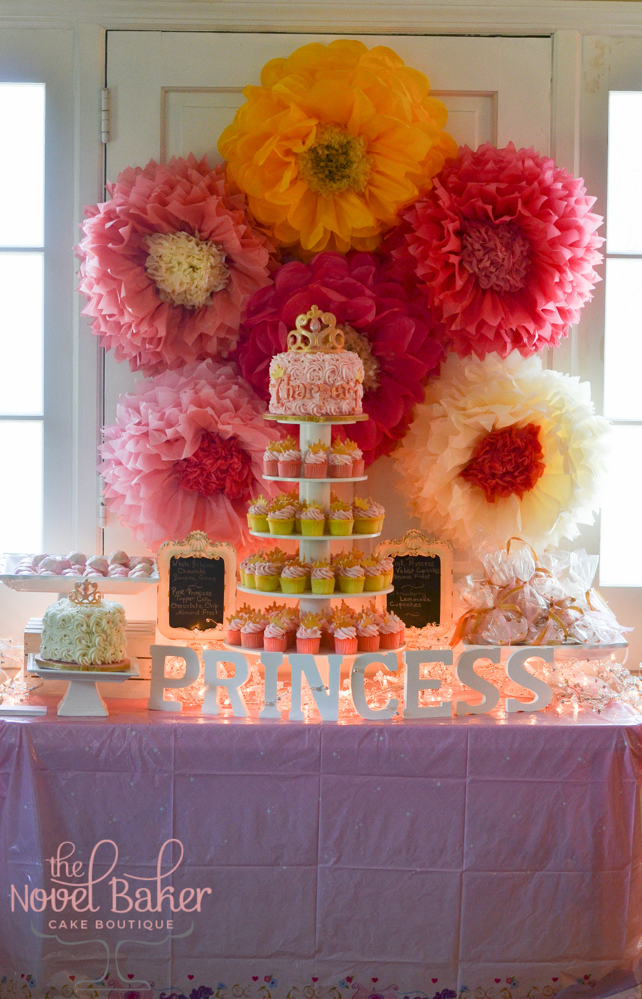 Party table with pink gems, crown favor cookies and smash cake along side a 5 Tier Cupcake tower filled with pink minis topped with gold crowns and a top tier Princess cake of pink rosettes, pearl centers, and a gold rubbed tiara.