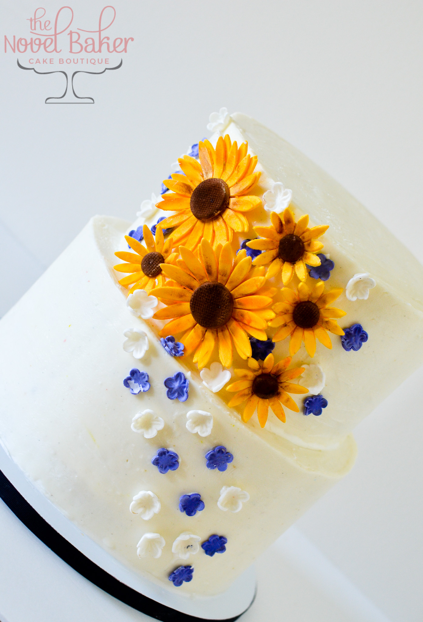 White two tier buttercream with Sunflower Cluster and tiny blue and white flowers