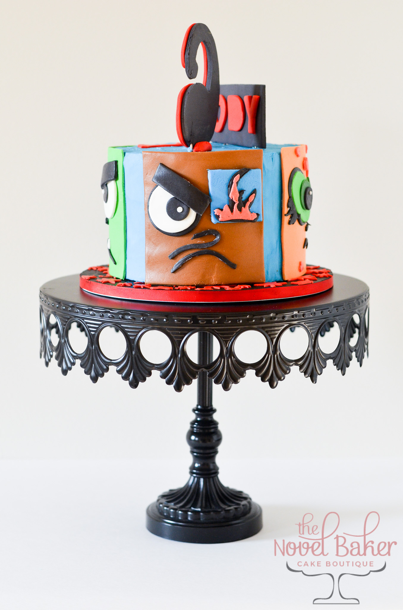 Single tier buttercream cake with 4 fondant panels wrapping the sides of the cake, each panel with eyes, nose, and mouth resembling a different TitanTeens Go Character.