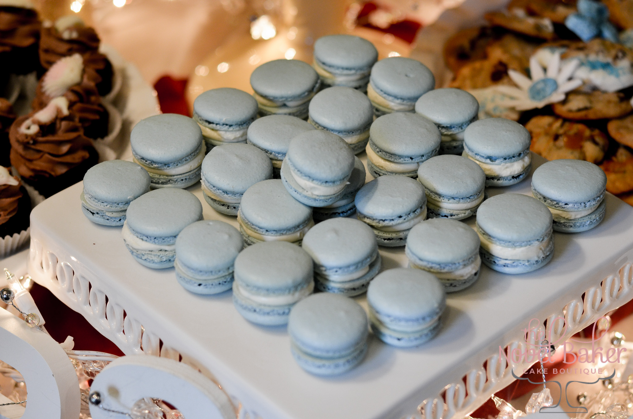 Rows of Sea Blue Macarons with white SMBC on a scalloped white pedestal