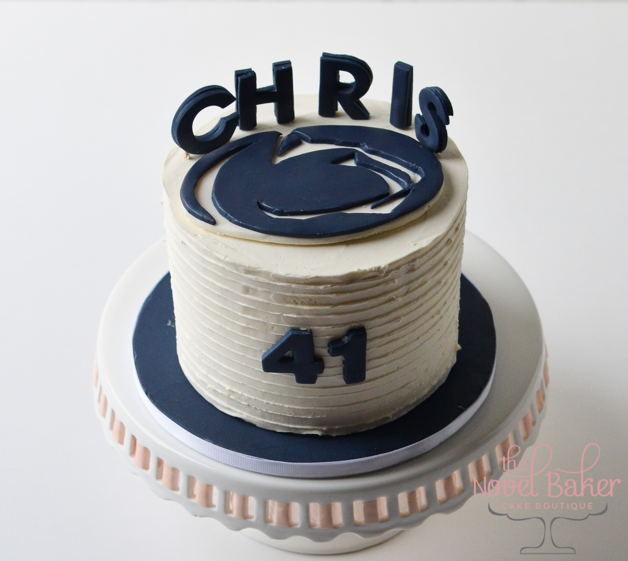 "PSU hand cut Nittany Lion flat plaque cake topper, navy ""Chris"" letters stand on top and a navy ""41"" on the cake's front"