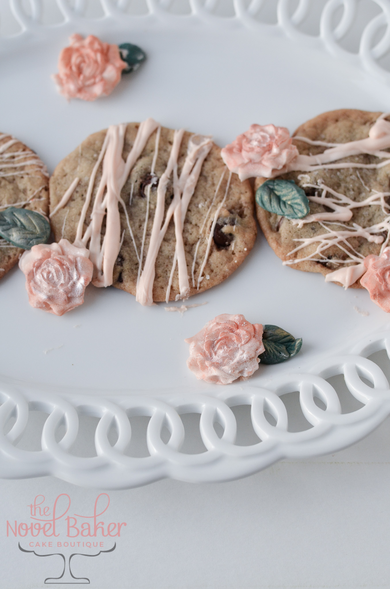 Chocolate Chip Cookies drizzled with white chocolate tinted peach with peach fondant roses/dark green fondant leaves on a scalloped edge white plate