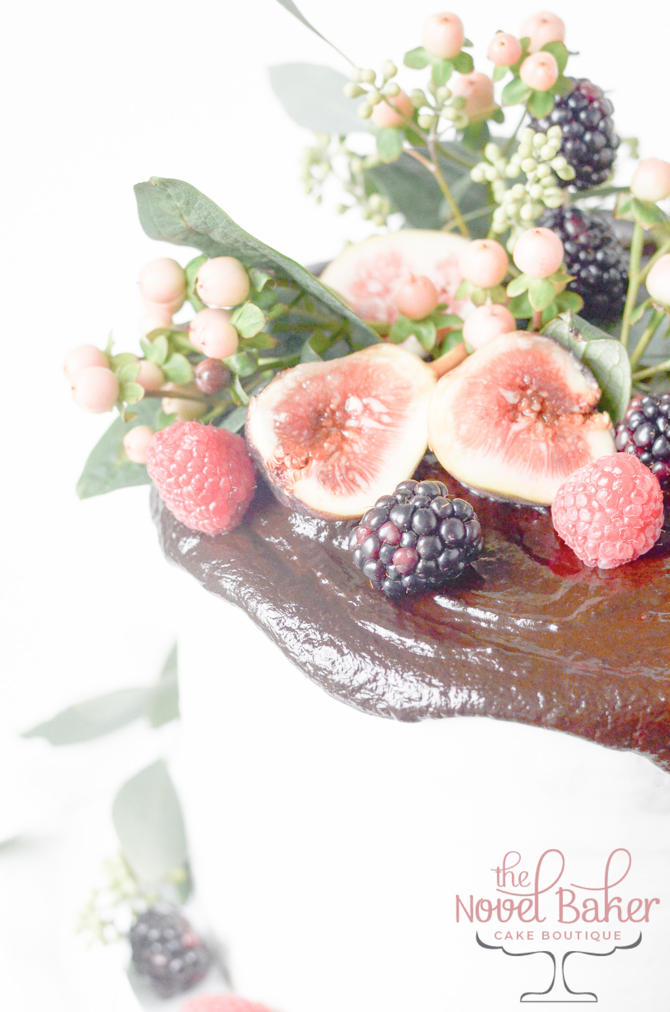 Semi Naked white buttercream over chocolate cake, chocolate ganache lid with fresg berries, figs, and eucalyptus