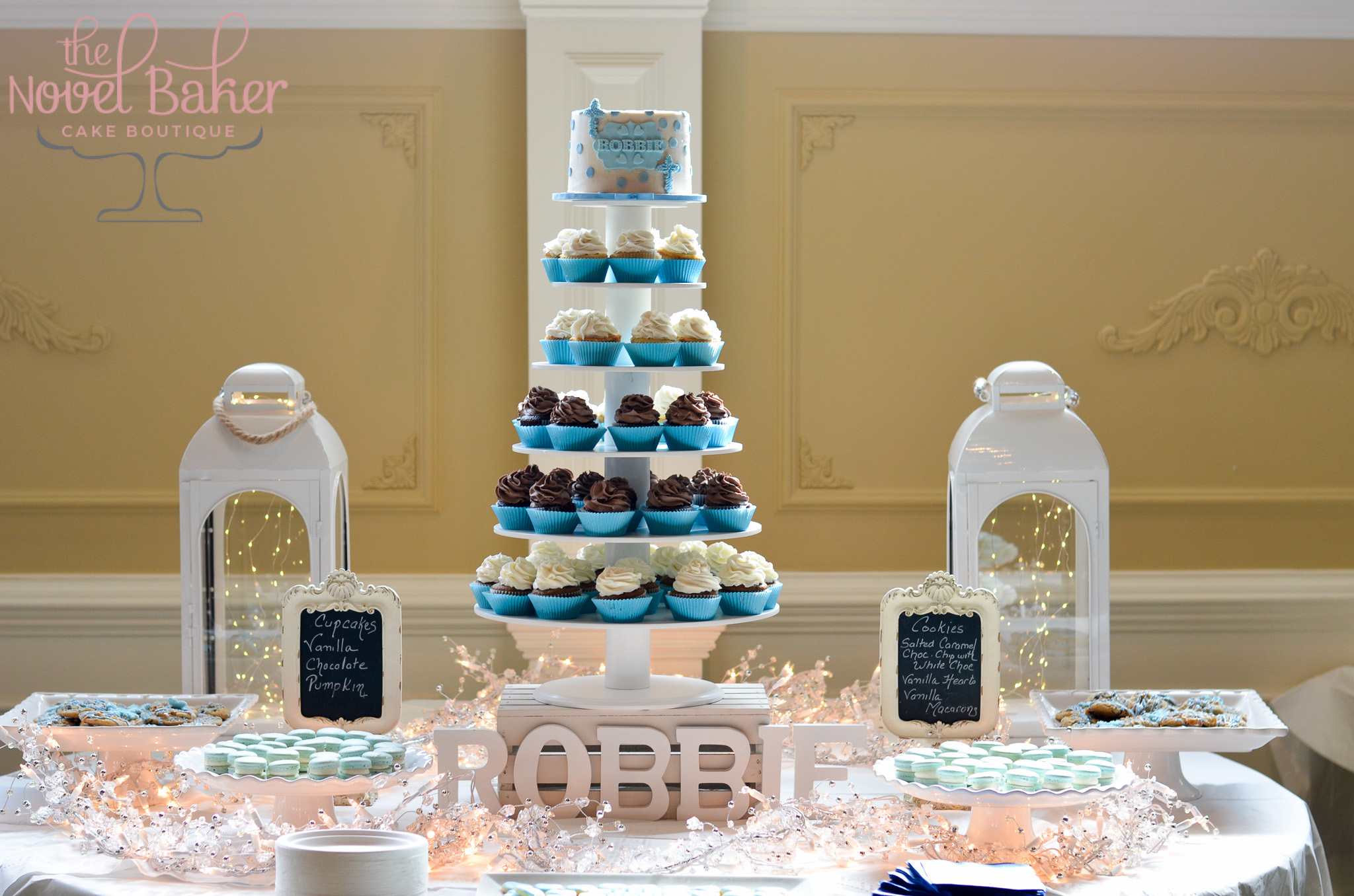 Baby Blue Sweet Table with macarons, chocolate drizzle chocolate chip cookies, petite heart sugar cookies, cupcake tower with vanilla and chocolate cupcakes in blue liners with a polka dot topper cake