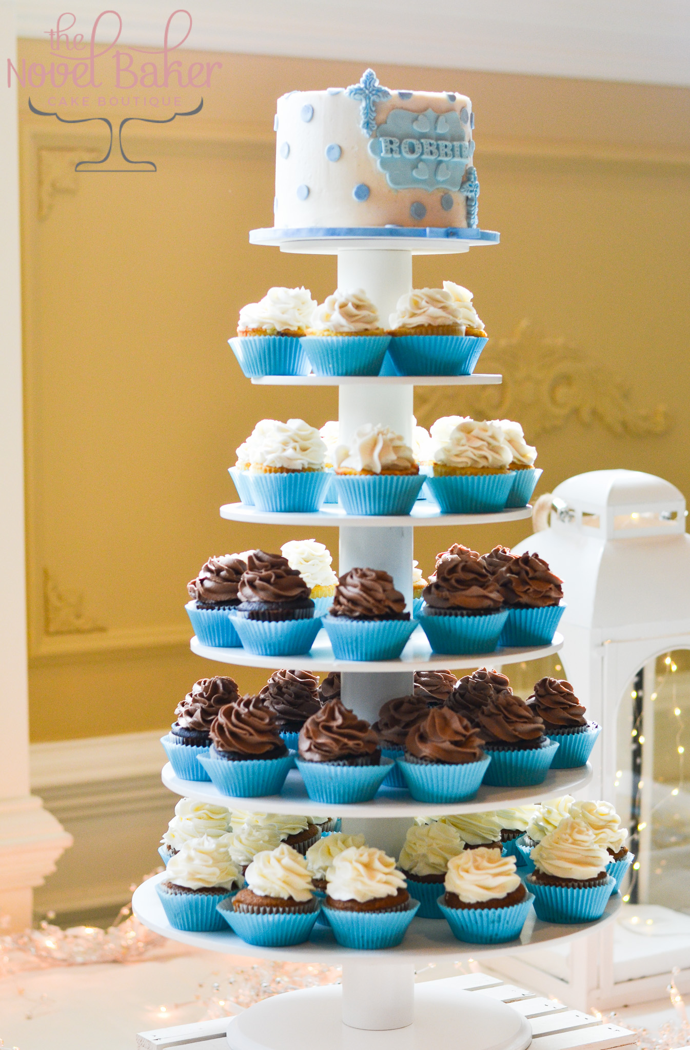 Chocolate and Vanilla Cupcakes in blue liners. a white topper cake with blue dots, name plaque and crosses.
