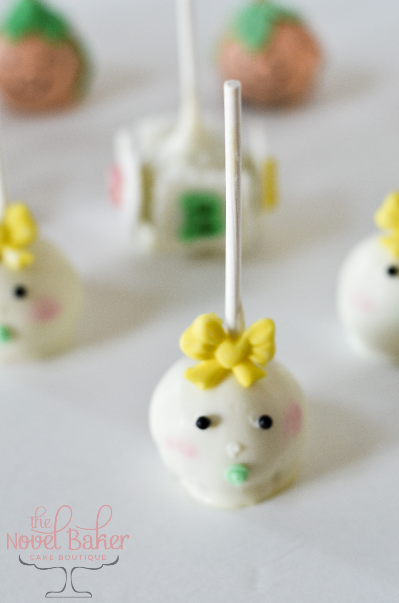 Baby Face CakePop with yellow bow and green binkey