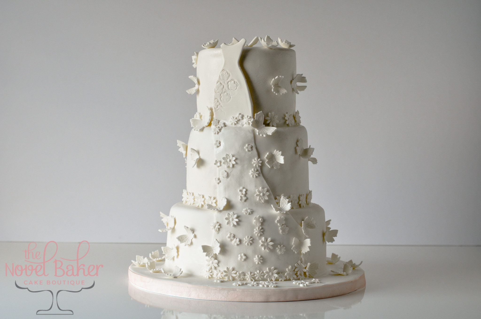 Three Tiers covered in white fondant with a white bridal gown cascading from top to bottom