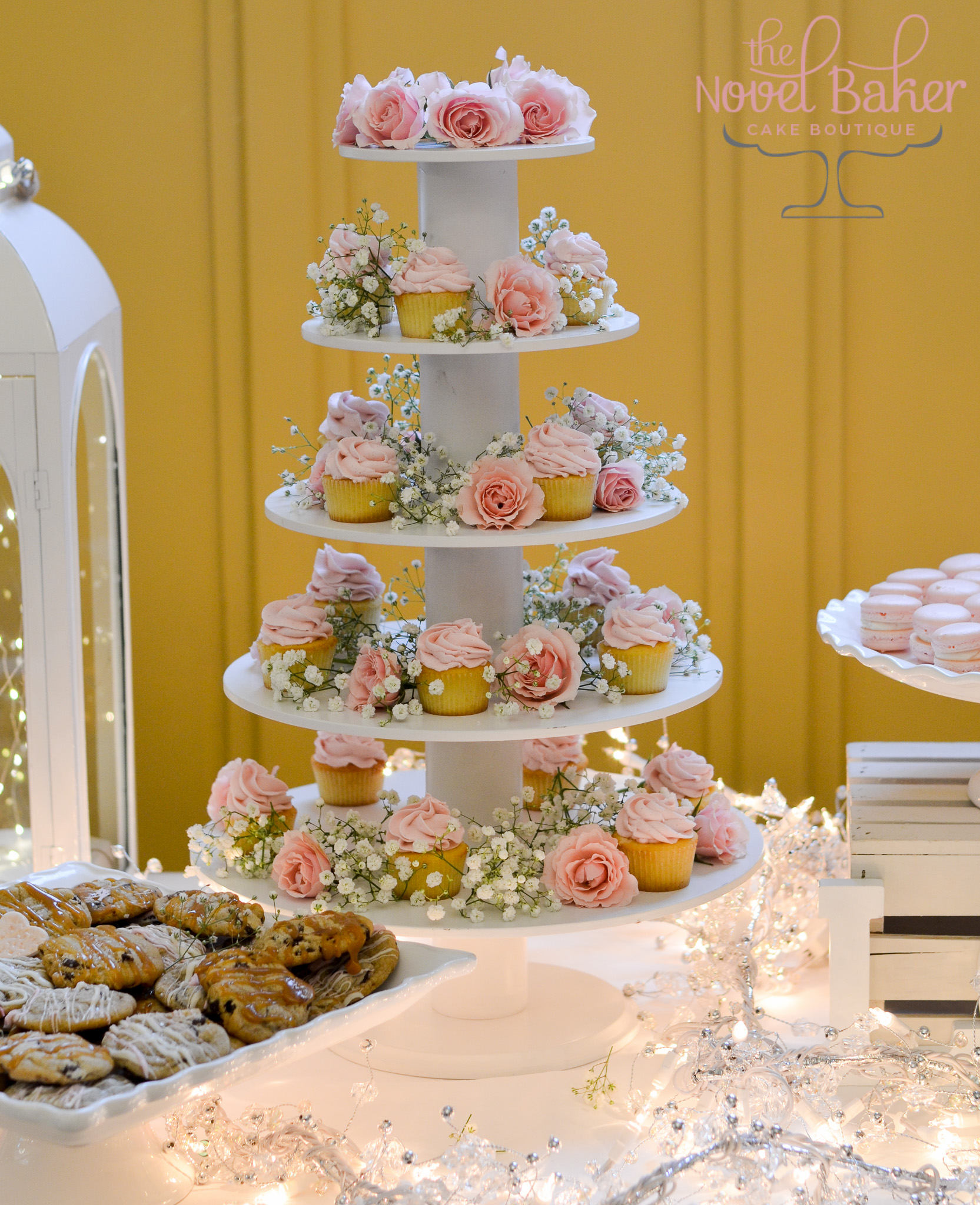 Vintage Roses and Baby's Breath arranged between mini pink champagne cupcakes  set on a cupcake tower with rose topper