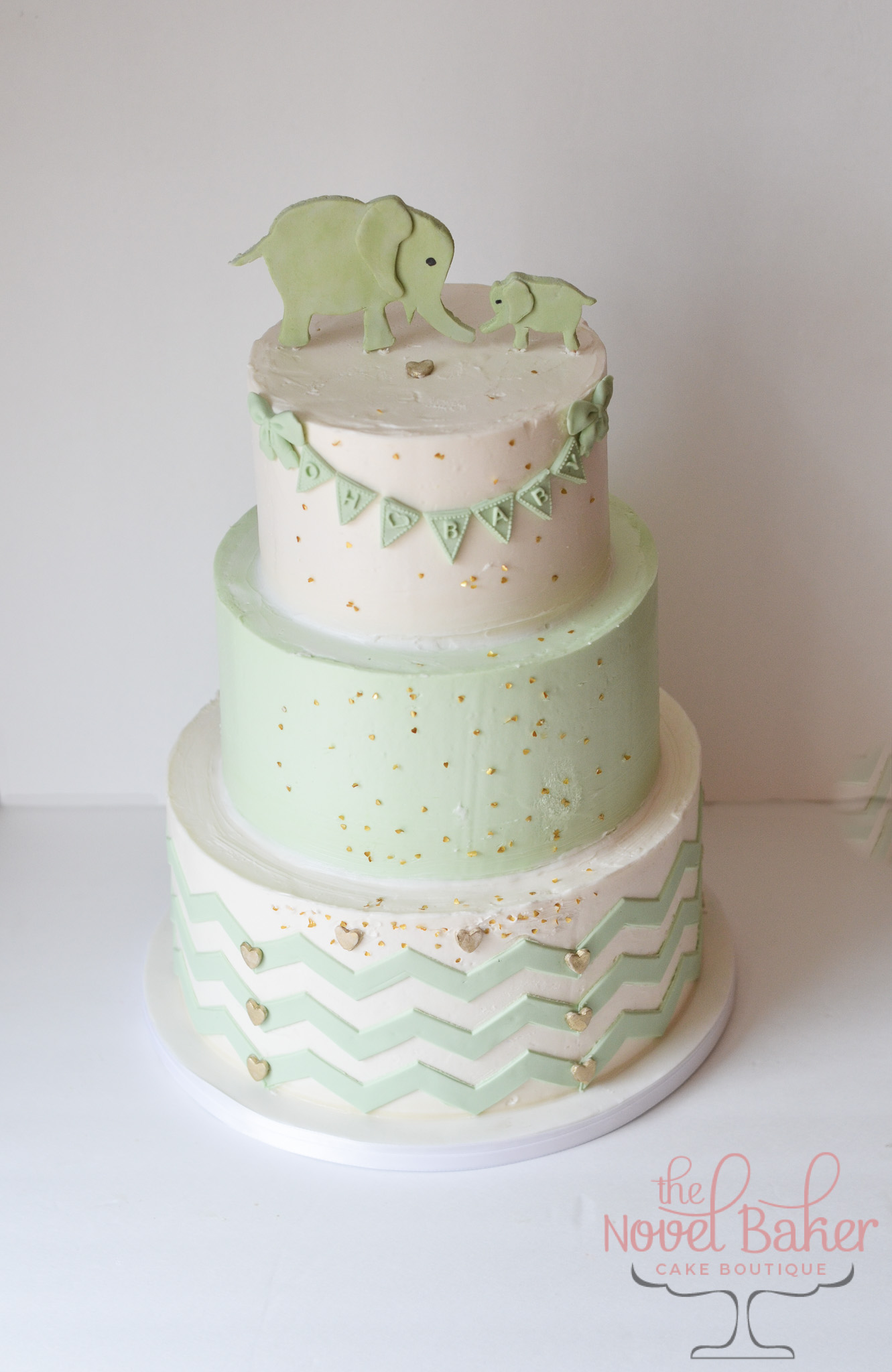"Three tier mint and white buttercream speckled with gold hearts is adorably gender neutral. Little bows tied on the ends of the ""oh baby"" bunting swipe the top tier while a chevron pattern graces the bottom tier. A one-dimensional mommy and baby elephant fondant topper in mint green crowns the tippy top of this stately baby shower cake."