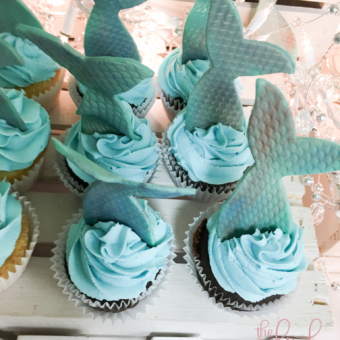 Cupcakes with a luscious oceany blue buttercream topped with extra large textured and shimmery fondant Mermaid Tails.