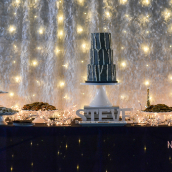 50th Birthday Party Table with a 3 tier Aspen Cake in Gray Buttercream surrounded by pedestals of cookies