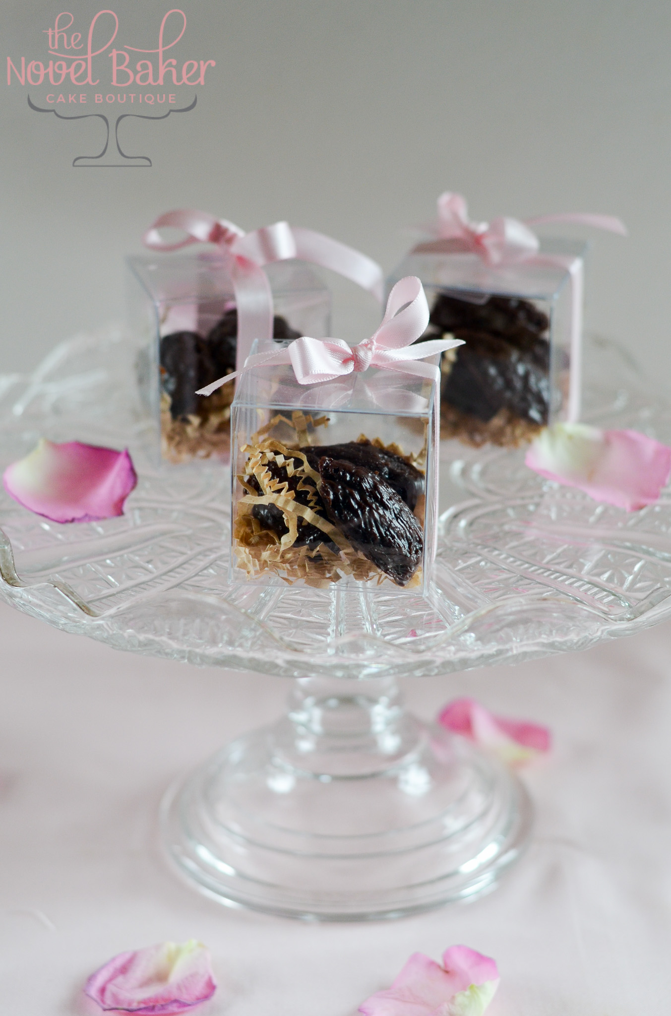 Mini Chocolate Madeleines in pink ribbon tied clear favor boxes