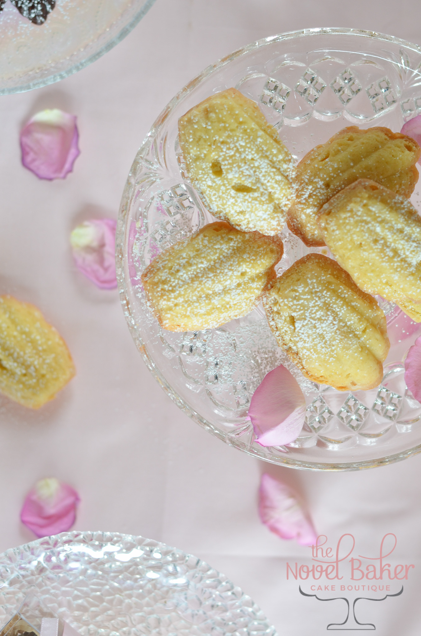 Lemon Madeleines sprinkled with sugar set upon a glass pedestal with rose petals