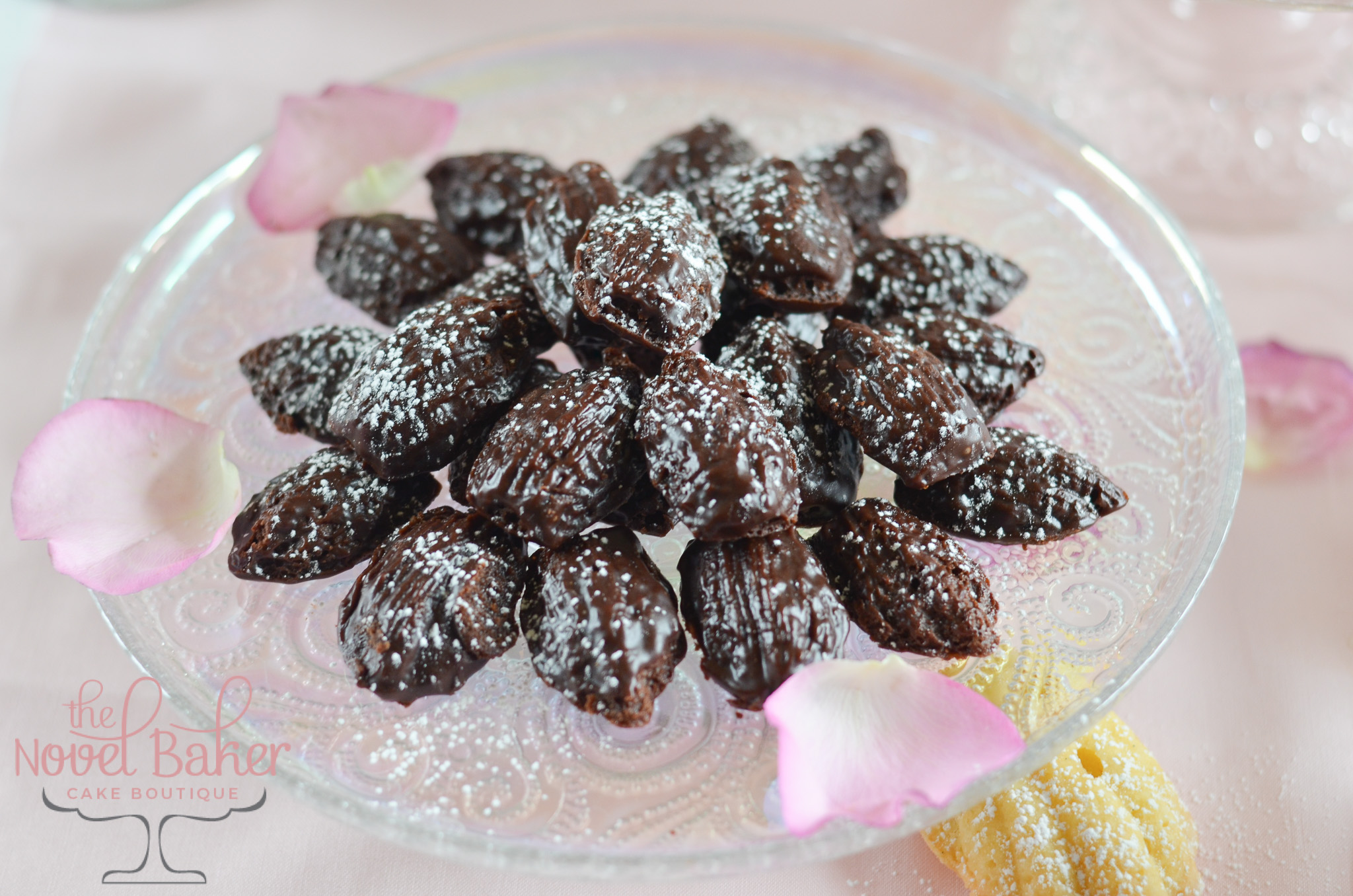 Mini Chocolate Madeleines sprinkled with sugar set upon a glass pedestal with rose petals