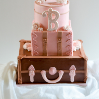 Luggage Cake in three tiers in blush and natural leather with roses, straps, and initials.