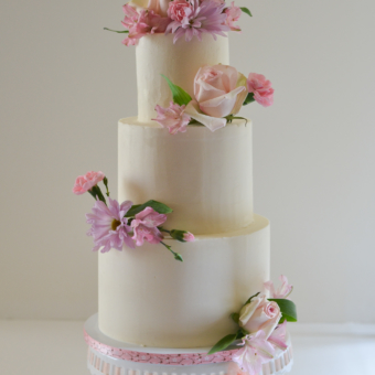 Fresh pink and lavender flowers on ivory buttercream in three tiers