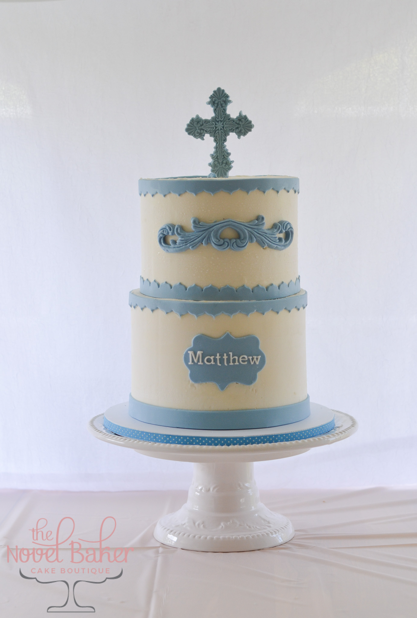 BoysTwo Tier Communion Cake in Ivory Buttercream with blue fondant details of borders, flourish, name plaque, and embossed cross topper.
