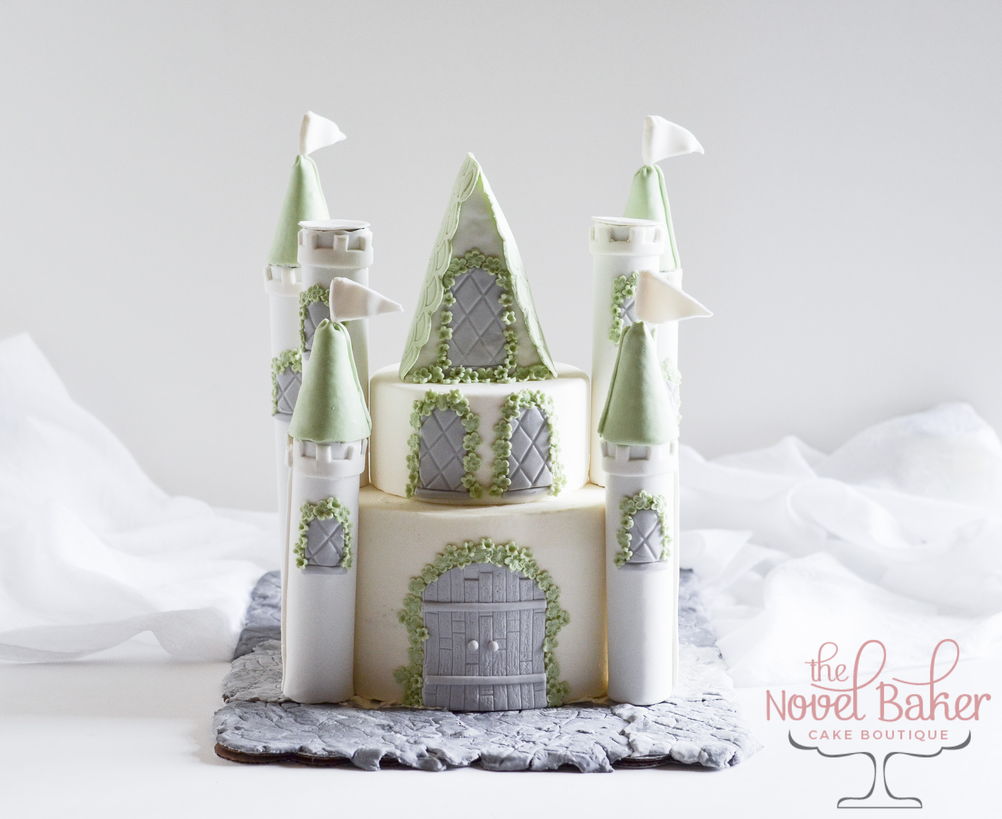 Fairy Tale Castle Cake in white buttercream with Fondant details -- gray diamond windows and wooden front door, mint flowers and mint turrets so they can live happily ever after.