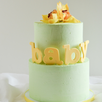 Sleek mint colored two-tier butttercream with oversized fondant lowercase letters in pale yellow with a fresh yellow orchid topper.