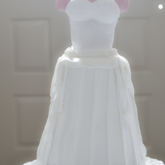 Three-dimensional bridal dress cake with white pearl necklace.