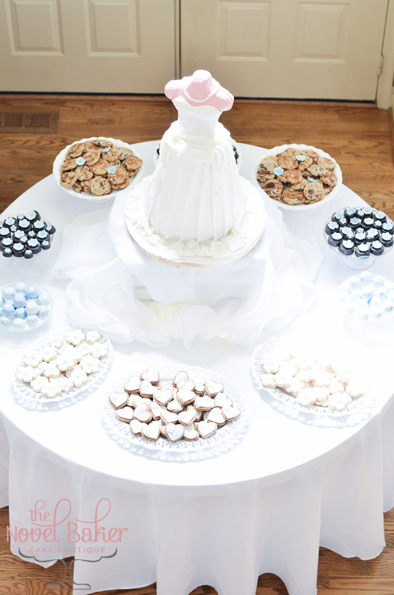 A 3-dimensional bride dress cake surrounded by pedestals and plates of cookies, all set out on a round table.