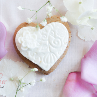 Gingerbread Hearts with white embossed fondant and a white buttercup flower nestled in the corner.