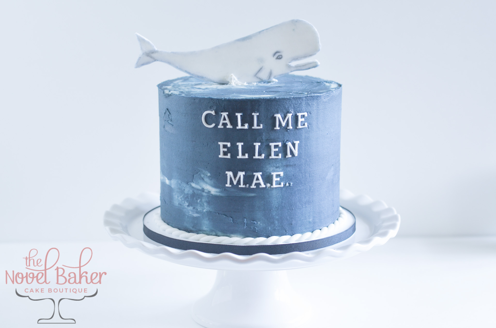 Deep Sea Blue buttercream single tier cake with a 2-dimensional whale topper of Moby Dick.