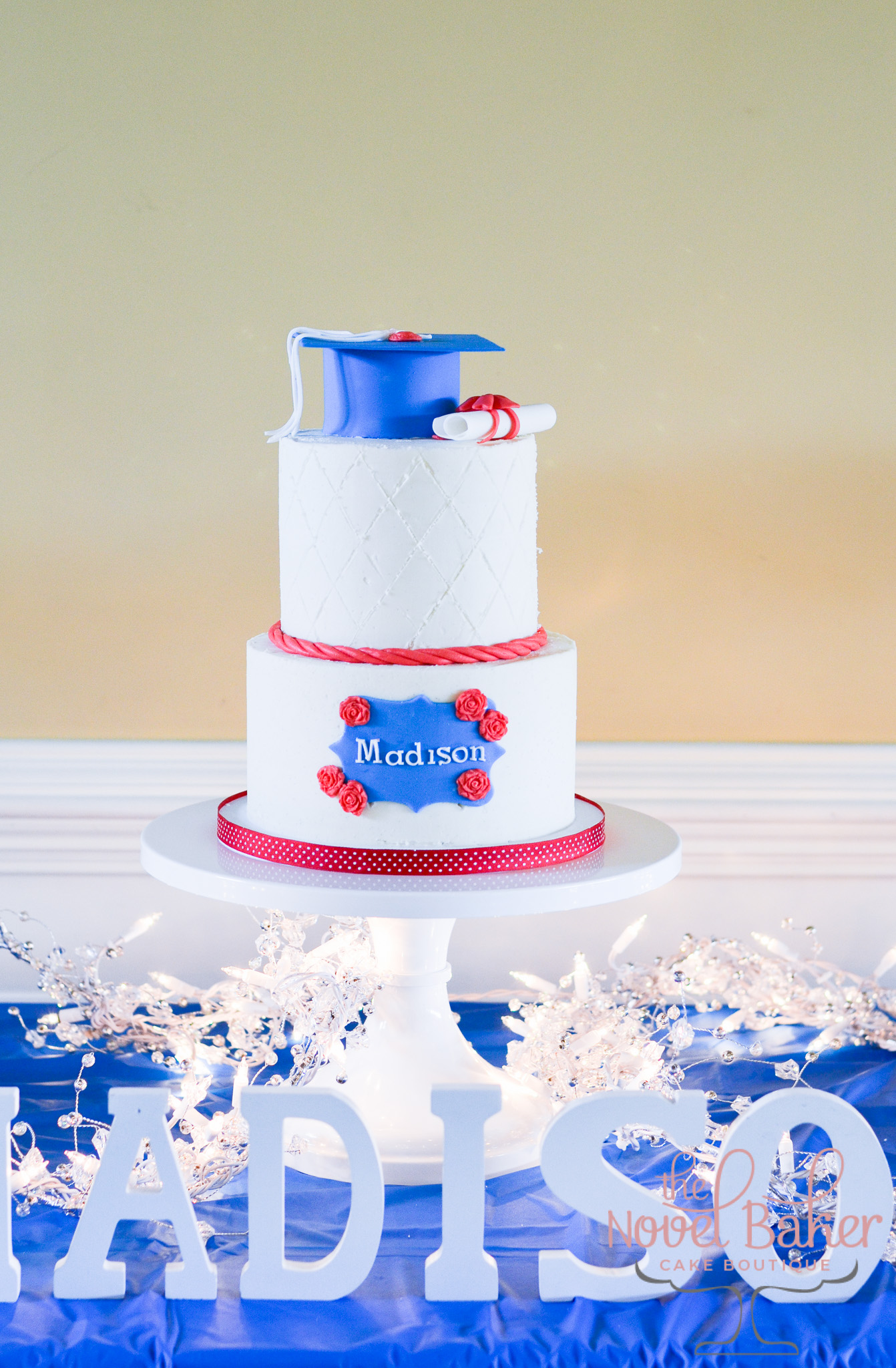 "Two-tier white buttercream with red trim, blue ""Madison"" name plaque embellished with roses. The topper is a blue grad cap with white tassel and red button next to a white diploma tied with a red ribbon."