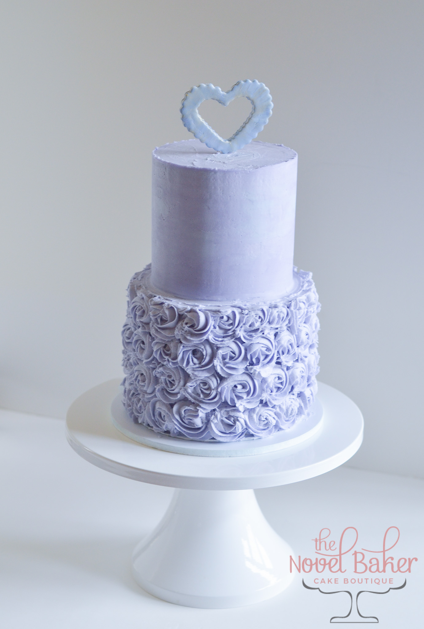 Two-tier lavender buttercream cake with a bottom tier of rosettes and a light blue peek-a-boo fondant heart topper.