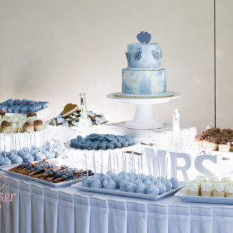 Sweet Table with Blue macarons, cake pops, pretzels and cookies with a two tier misty blue focal cake.