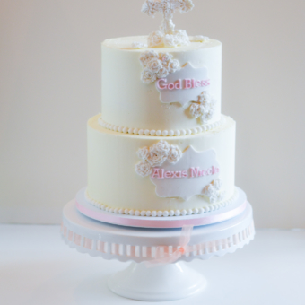 Two-tier buttercream cake with white pearl border, white filigree cross topper, tiny white roses, white plaque, and pink writing.