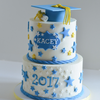 Two-Tier Buttercream cake with white, blue, and yellow stars, topped with a blue grad hat with yellow tasle and white diploma tied with a yellow ribbon
