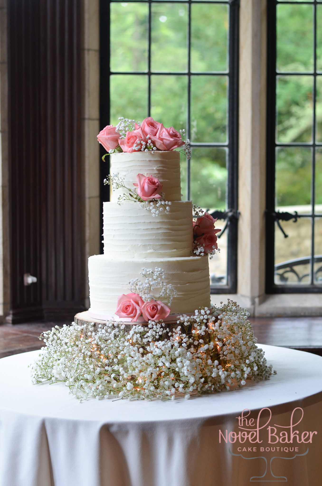 Three-tier rustic buttercream wedding cake with pink roses and baby's breath. The base is a natural tree trunk surrounded with baby's breath sparkling with fairy lights.