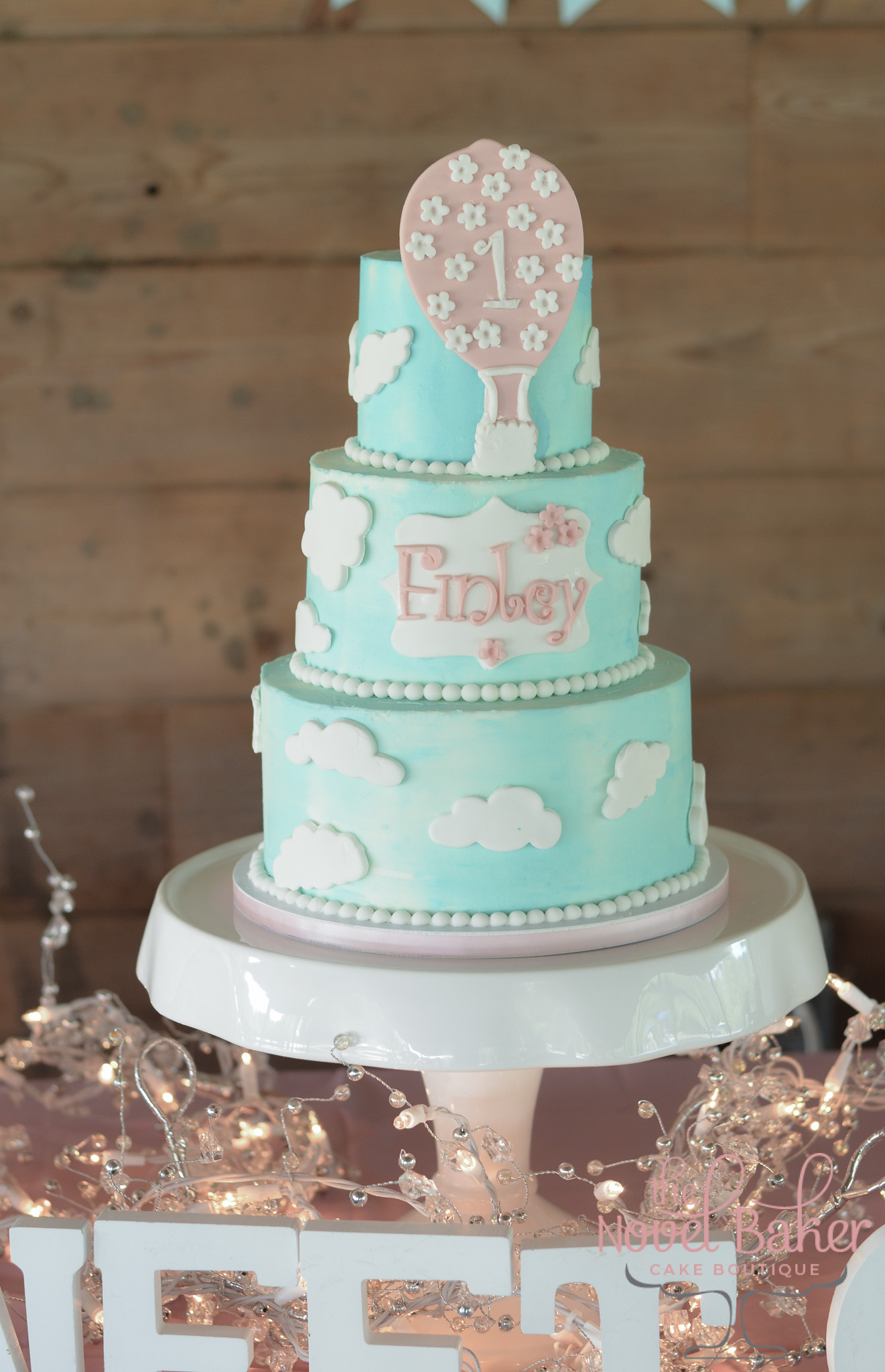 "Turquoise Sky three tier buttercream cake with white fondant clouds. ""Finley"" name plaque and Pink Hot air baloon with ""1"" and tiny flowers."