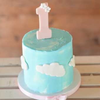 "Smash cake with Turquoise sky and white fondant clouds. Pink Fondant ""1"" topper with tiny flowers."