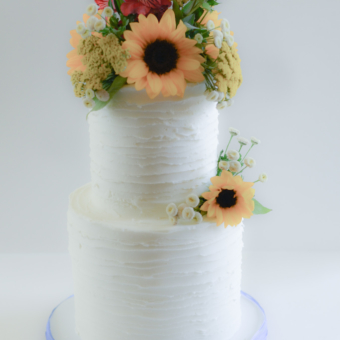 Two tier white buttercream with fresh sunflowers and wilfdflowers
