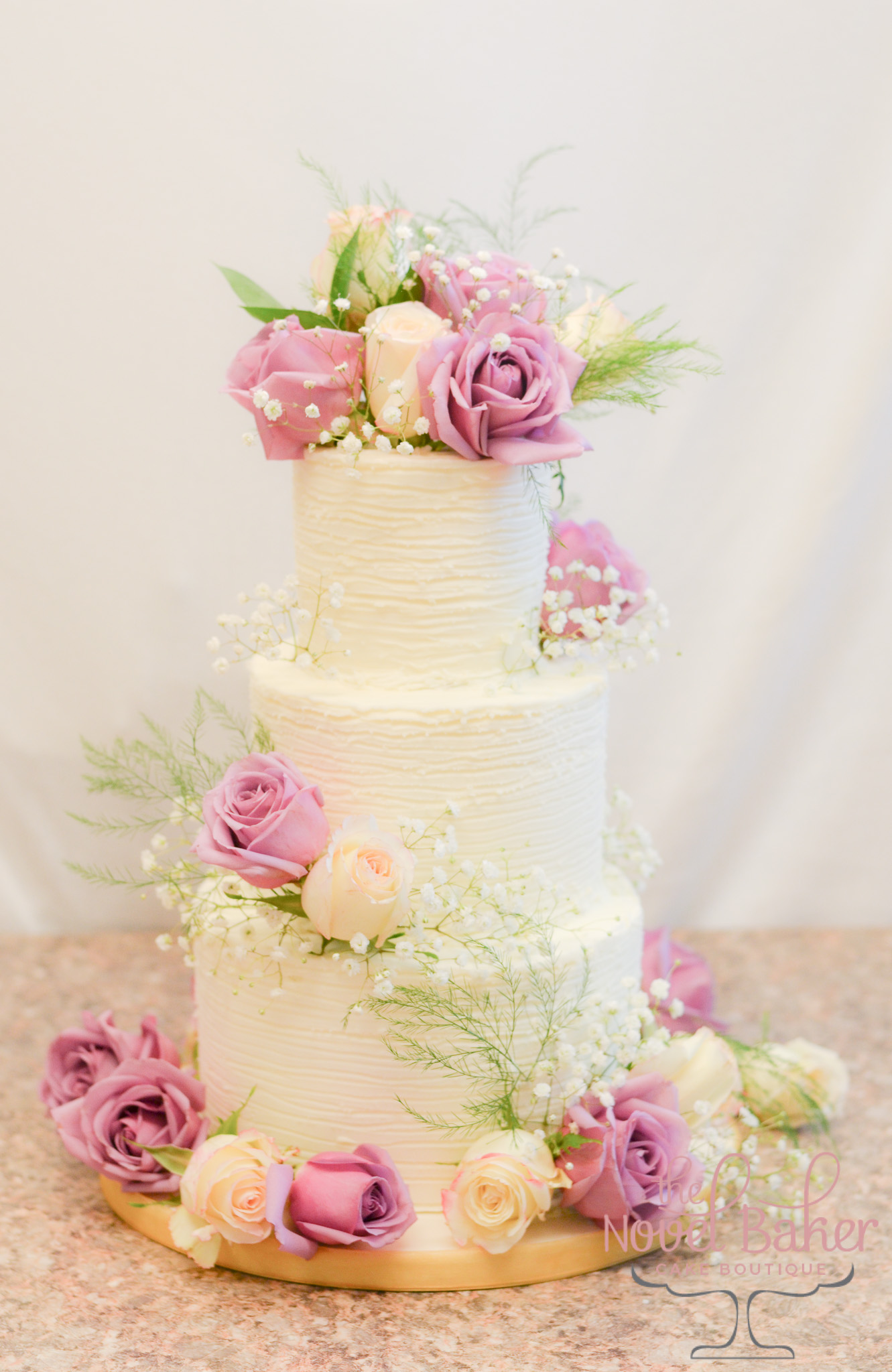 Three-tiered buttercream wedding cake with lavender roses